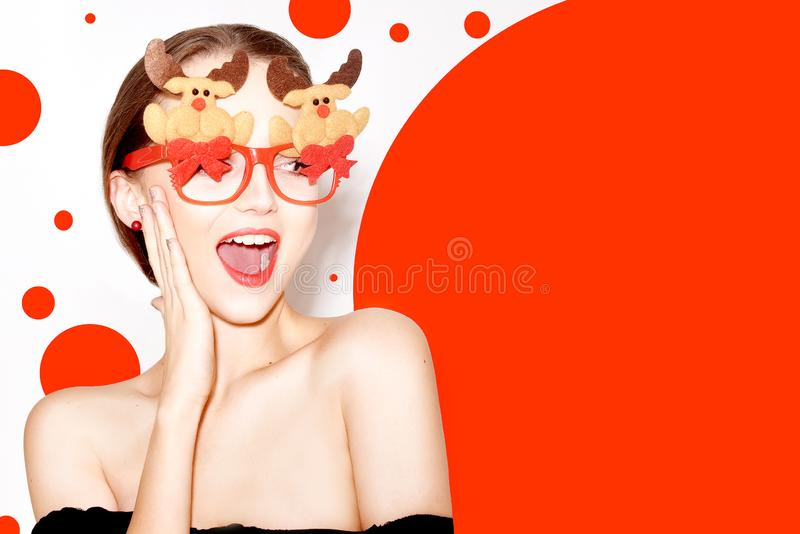 Beautiful stylish girl in black outfit celebrating new year. Girl in funny glasses with new year`s deer and bows. Model smile royalty free stock images