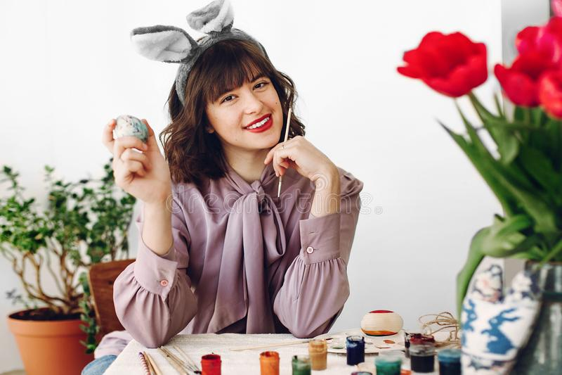 Beautiful stylish girl in bunny ears smiling and painting easter. Eggs on rustic table with tulips and paint in home with space for text. woman having fun royalty free stock photography