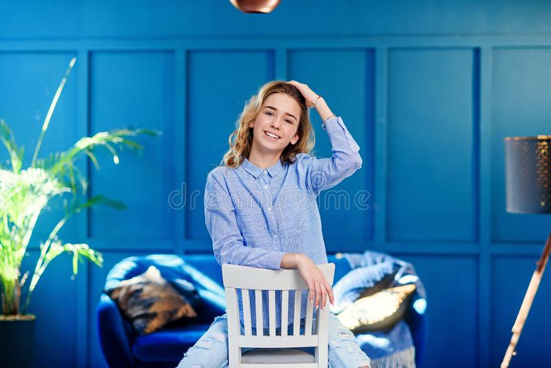 Beautiful stylish girl in casual clothes sits on a white wooden chair in stylish modern interior with blue background. stock images