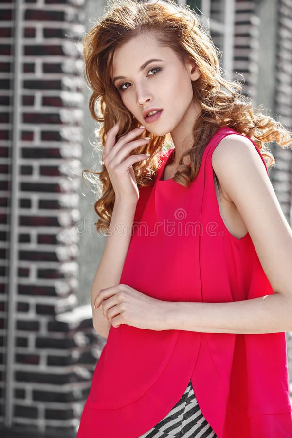 Beautiful stylish girl dressed in fuchsia color top and black and white skirt poses in the city street on a summer day royalty free stock images