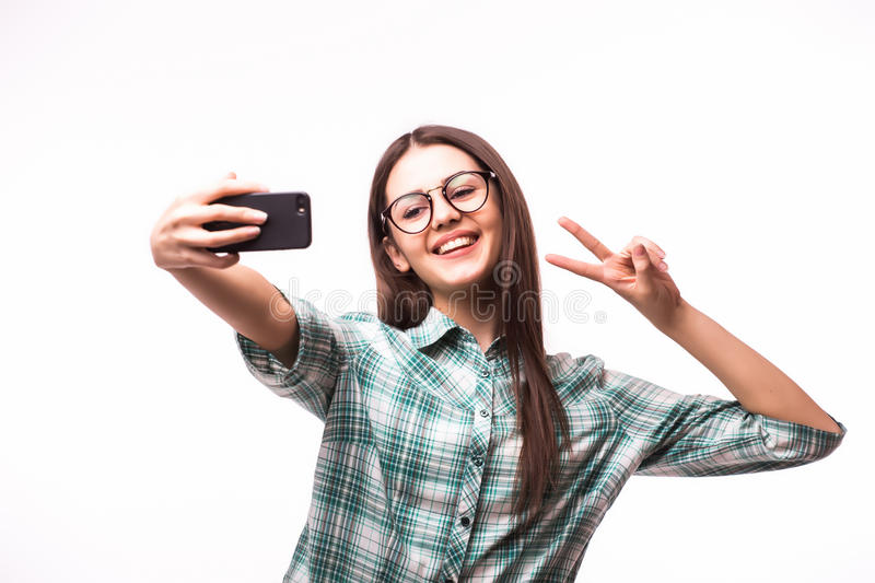 Beautiful stylish girl making selfie with victory gesture. On whitel background stock photos