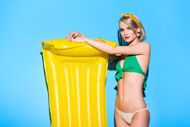 beautiful stylish girl posing in bikini with yellow inflatable mattress royalty free stock image