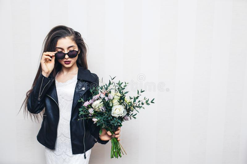 Beautiful stylish girl in sunglasses, dressed in leather jacket, holding bouquet of flowers and posing on white wall. Beautiful stylish girl in sunglasses royalty free stock photography