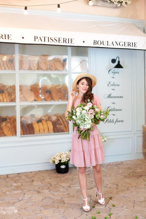 Beautiful stylish girl in a vintage dress and straw hat in the interior of a French bakery. Cheerful girl with brown hair gladly r stock images
