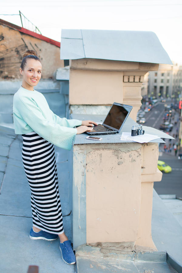 Beautiful and stylish girl works for a laptop on the roof of the house in the old town. on the table are also documents and old ca stock images