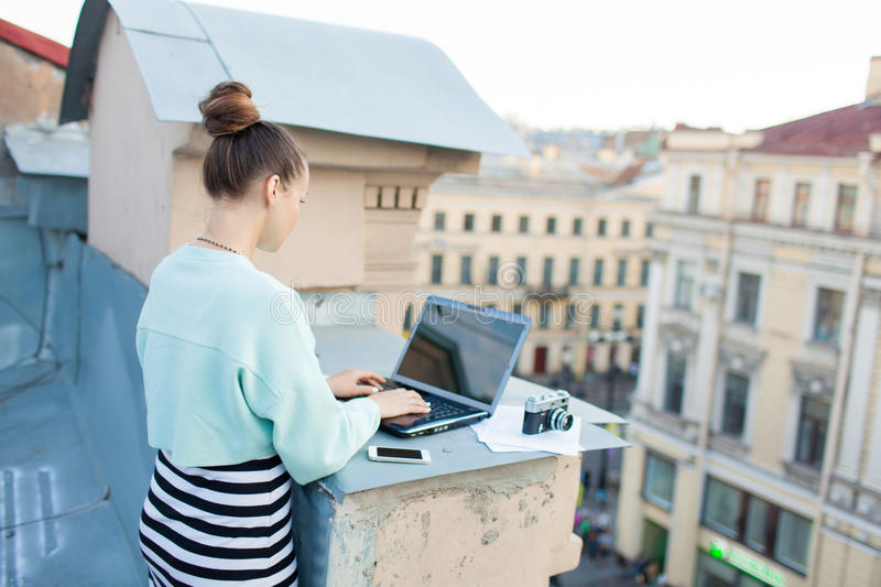 Beautiful and stylish girl works for a laptop on the roof of the house in the old town. on the table are also documents and old ca royalty free stock photo