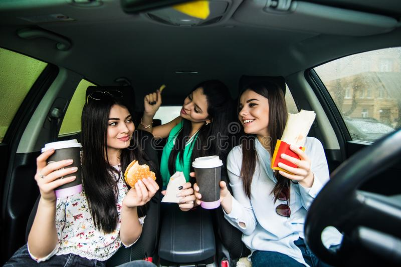 Beautiful stylish girls are making selfie eating fast food and having fun while sitting in the car stock photography