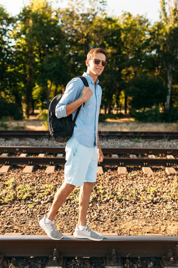 Beautiful stylish guy with glasses, posing on the rails of the train at sunset, hipster posing in stylish clothes, for advertising. Beautiful stylish guy with royalty free stock photos