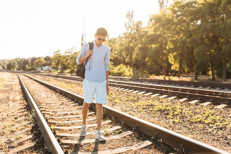 Beautiful stylish guy with glasses, posing on the rails of the train at sunset, hipster posing in stylish clothes, for advertising. Beautiful stylish guy with royalty free stock image