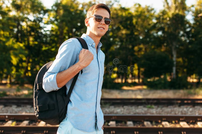 Beautiful stylish guy with glasses, posing on the rails of the train at sunset, hipster posing in stylish clothes, for advertising. Beautiful stylish guy with royalty free stock photo