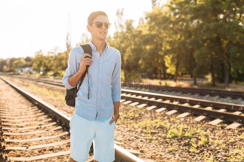Beautiful stylish guy with glasses, posing on the rails of the train at sunset, hipster posing in stylish clothes, for advertising. Beautiful stylish guy with royalty free stock images