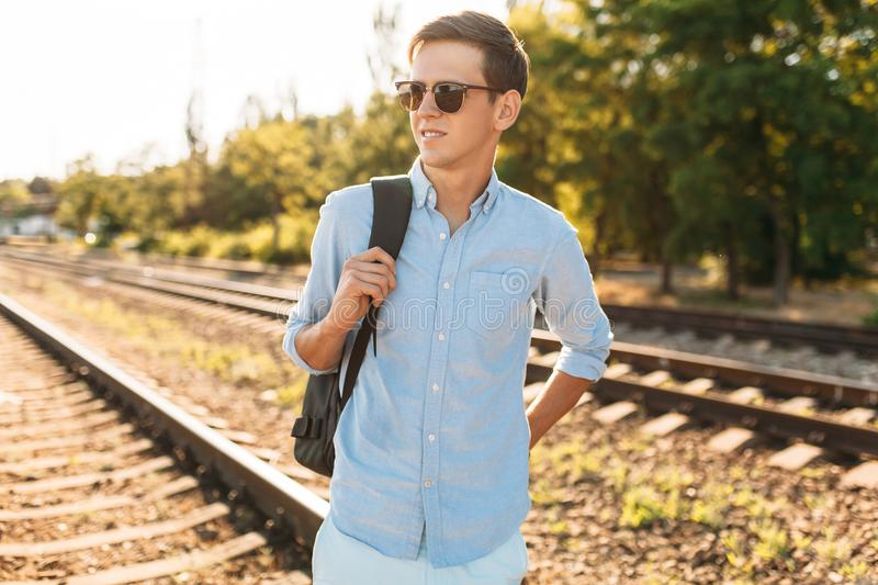Beautiful stylish guy with glasses, posing on the rails of the train at sunset, hipster posing in stylish clothes, for advertising. Beautiful stylish guy with stock photos