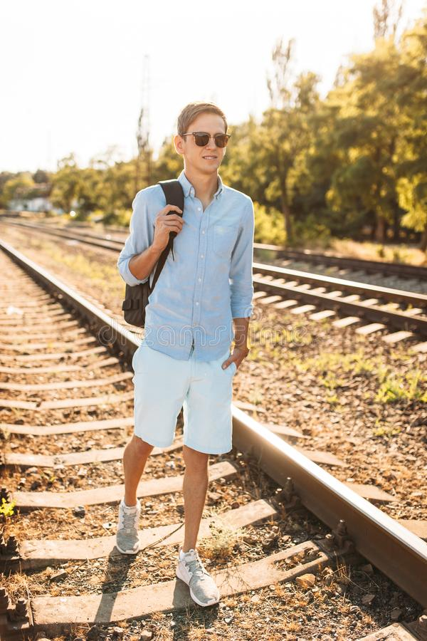 Beautiful stylish guy with glasses, posing on the rails of the train at sunset, hipster posing in stylish clothes, for advertising. Beautiful stylish guy with stock images