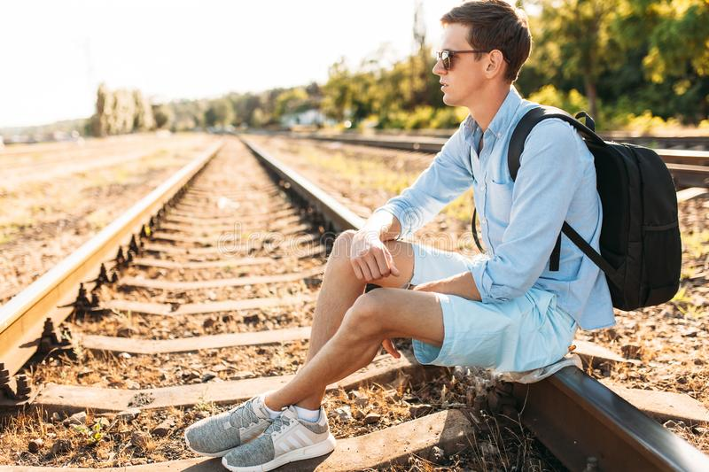 Beautiful stylish guy with glasses, posing sitting on the rails of the train at sunset, hipster posing in stylish clothes, for adv. Beautiful stylish guy with royalty free stock images