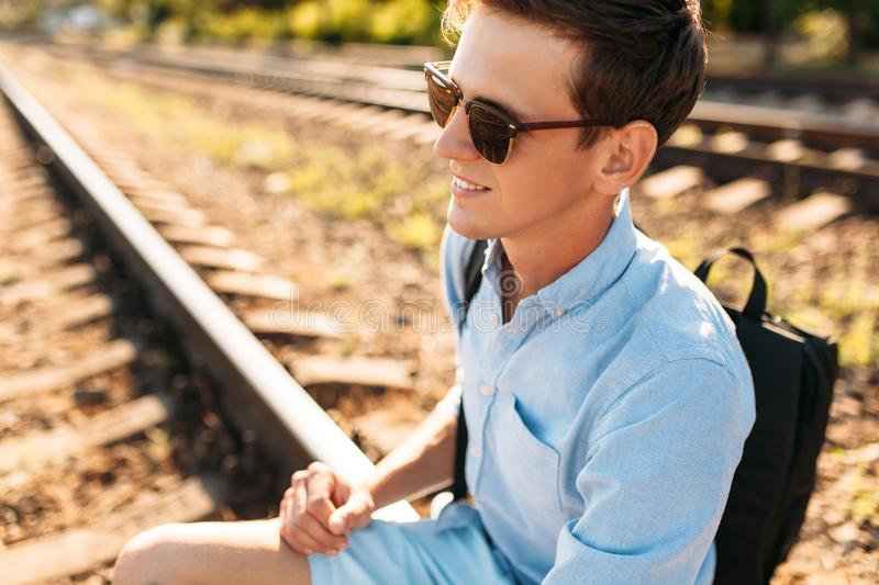 Beautiful stylish guy with glasses, posing sitting on the rails of the train at sunset, hipster posing in stylish clothes, for adv. Beautiful stylish guy with stock photos