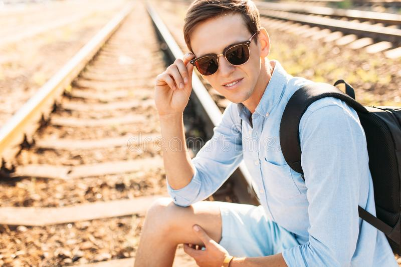 Beautiful stylish guy with glasses, posing sitting on the rails of the train at sunset, hipster posing in stylish clothes, for adv. Beautiful stylish guy with stock photo