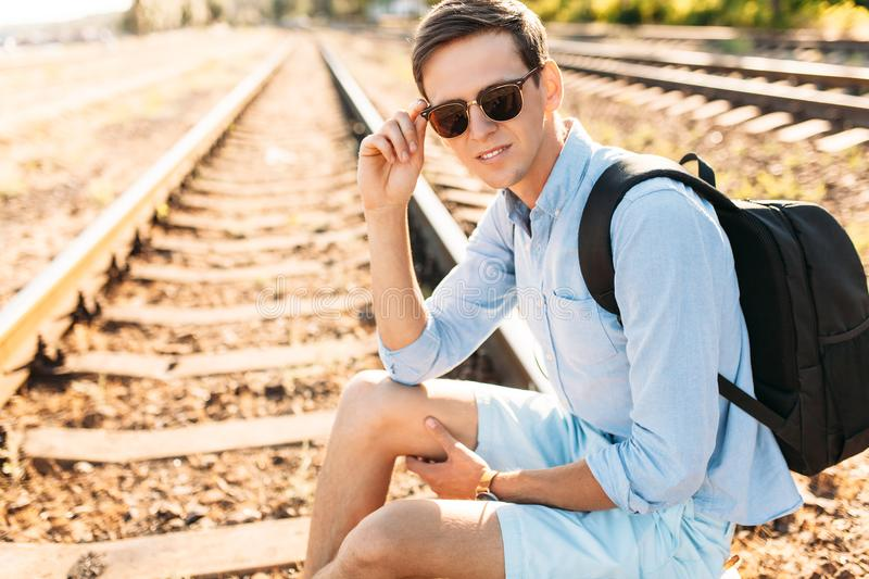 Beautiful stylish guy with glasses, posing sitting on the rails of the train at sunset, hipster posing in stylish clothes, for adv. Beautiful stylish guy with royalty free stock photography