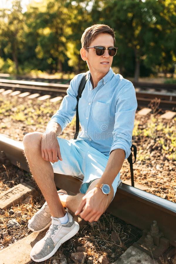 Beautiful stylish guy with glasses, posing sitting on the rails of the train at sunset, hipster posing in stylish clothes, for adv. Beautiful stylish guy with stock photography