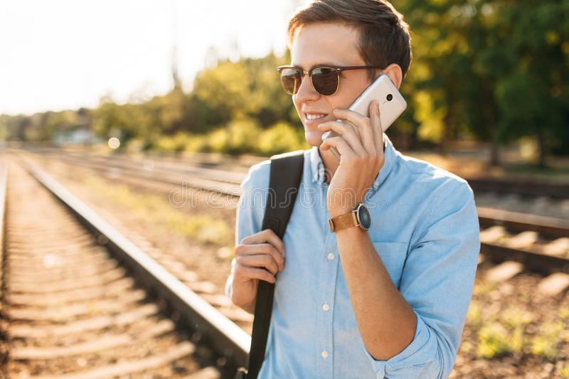 Beautiful stylish guy with glasses, posing on the train rails at sunset, and talking on the phone, hipster posing in stylish cloth. Es royalty free stock photo