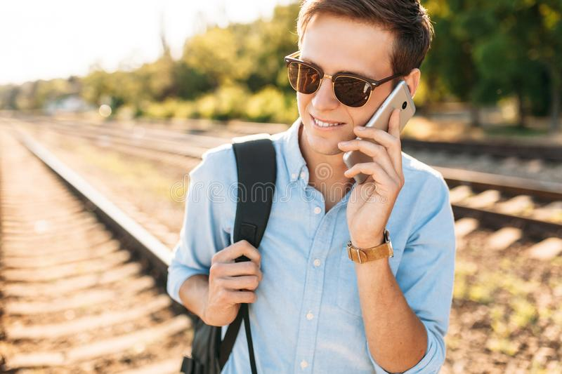 Beautiful stylish guy with glasses, posing on the train rails at sunset, and talking on the phone, hipster posing in stylish cloth. Es stock photo