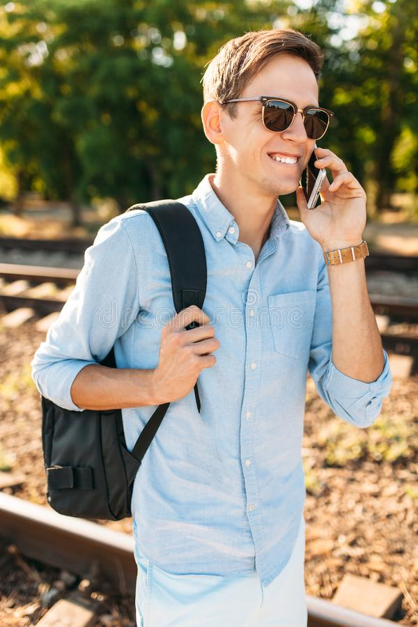 Beautiful stylish guy with glasses, posing on the train rails at sunset, and talking on the phone, hipster posing in stylish cloth. Es royalty free stock photography