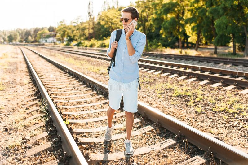 Beautiful stylish guy with glasses, posing on the train rails at sunset, and talking on the phone, hipster posing in stylish cloth. Es royalty free stock image