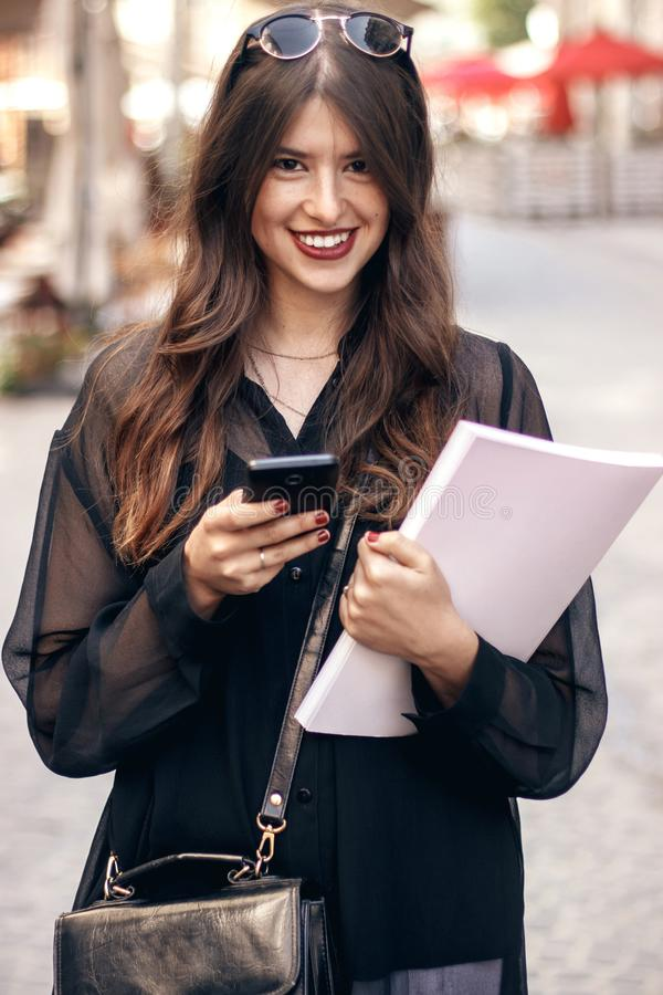beautiful stylish hipster girl texting on phone, smiling in sunny city street, holding magazine. happy gorgeous woman, dressed in stock photo
