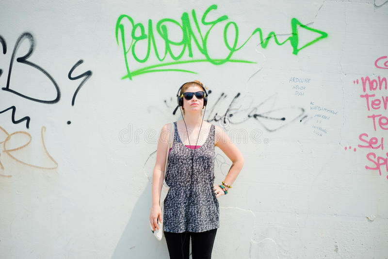 Beautiful stylish modern young woman listening to music royalty free stock photography