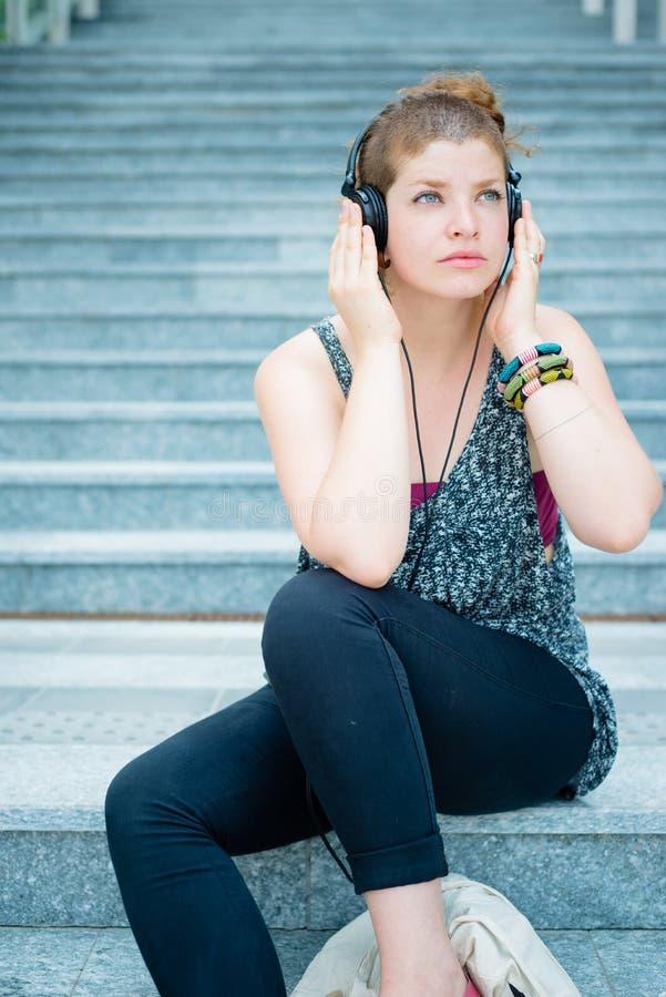 Beautiful stylish modern young woman listening to music stock photo