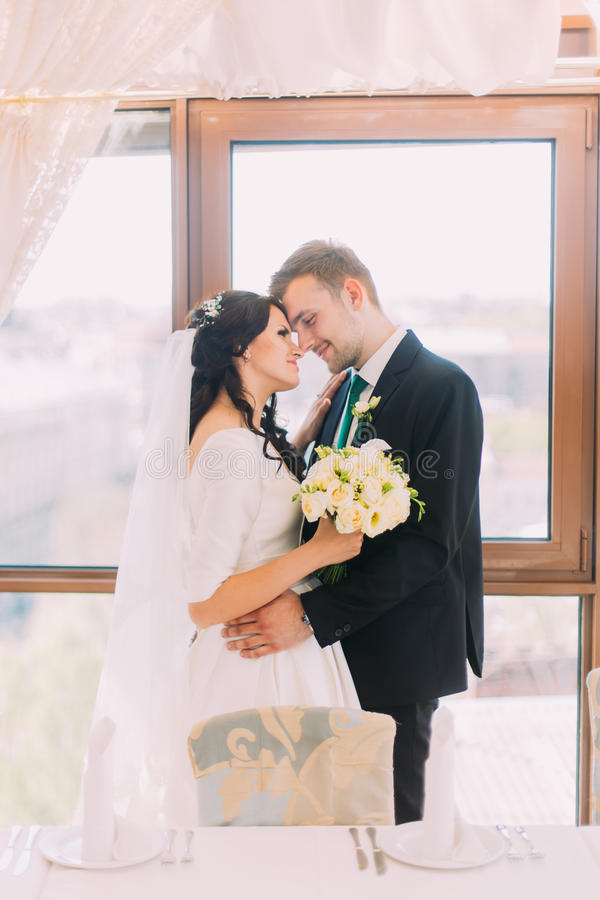 Beautiful stylish pair of newlyweds embracing each other in luxurious restaurant interior. Bright window as background.  stock photo