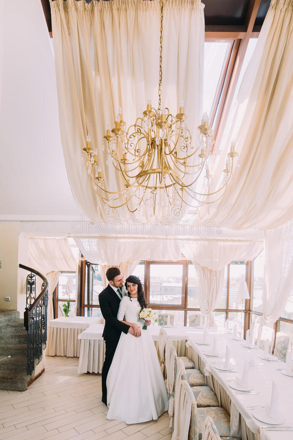 Beautiful stylish pair of newlyweds hugging in luxurious restaurant interior royalty free stock photography