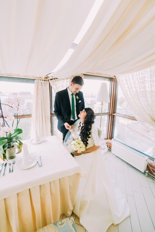 Beautiful stylish pair of newlyweds sharing loving stares in luxurious restaurant interior stock image