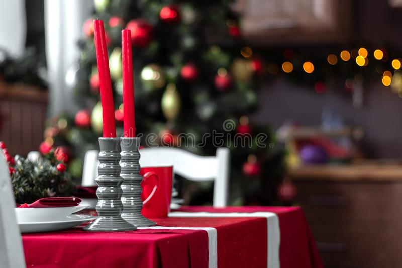 Beautiful and stylish table setting with Christmas decorations in living room, red candles and blurred background with fir tree stock image