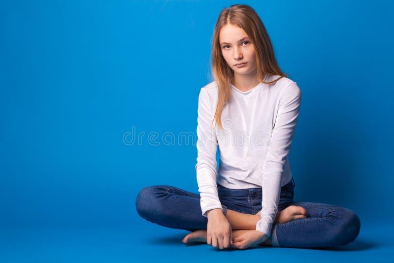 Beautiful stylish teen girl on blue background. royalty free stock photography