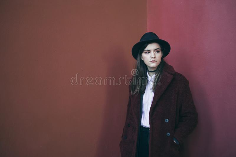 Beautiful stylish teenager girl in hat and red fur coat. Red calm sadness mood. problem solving. Fashion street style. Beautiful stylish teenager girl in hat and stock images