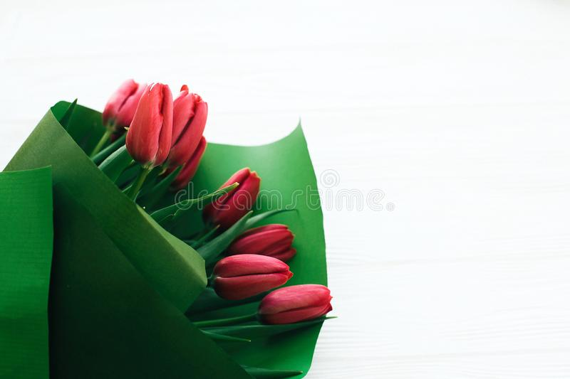Beautiful stylish tulips bouquet in green paper on white wooden background, top view. Pink tulips on white wood with space for royalty free stock photo