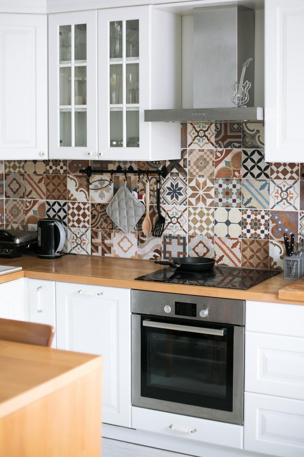 Beautiful stylish white real kitchen in Scandinavian style with wooden top and Spanish tiles royalty free stock images