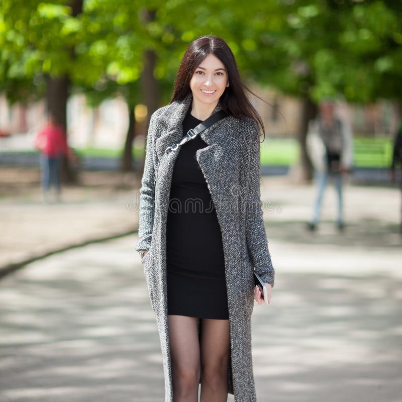 Beautiful stylish woman in black dress and cozy trench coat walk in city park. Spring outdoor lifestyle. Happy woman walking. Street style, trendy outfit stock photos