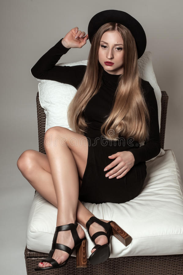 Beautiful stylish woman with blonde long hair in black dress and hat. Beautiful stylish young woman with blonde long hair in black dress and hat sitting on a royalty free stock image