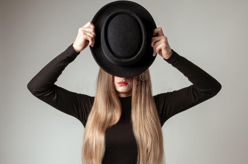 Beautiful stylish woman with blonde long hair in black dress and hat. Beautiful stylish young woman with blonde long hair in black dress with hat in studio royalty free stock photography