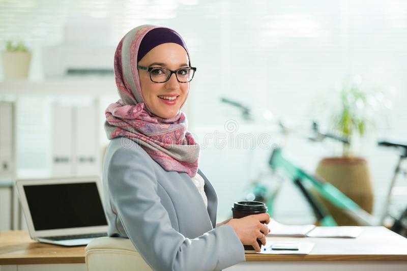 Beautiful stylish woman in hijab and eyeglasses, sitting at desk with laptop in office. Portrait of confident muslim businesswoman. Modern office with big stock image