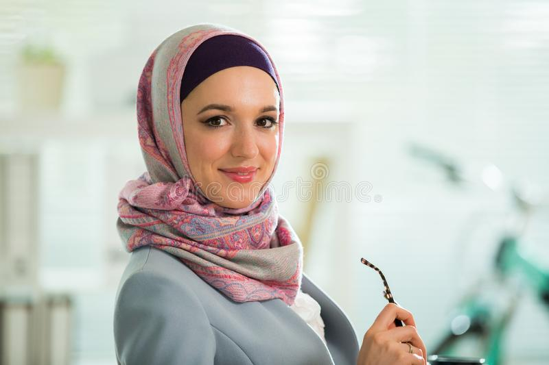 Beautiful stylish woman in hijab and eyeglasses, sitting at desk with laptop in office. Portrait of confident muslim businesswoman. Modern office with big royalty free stock photography