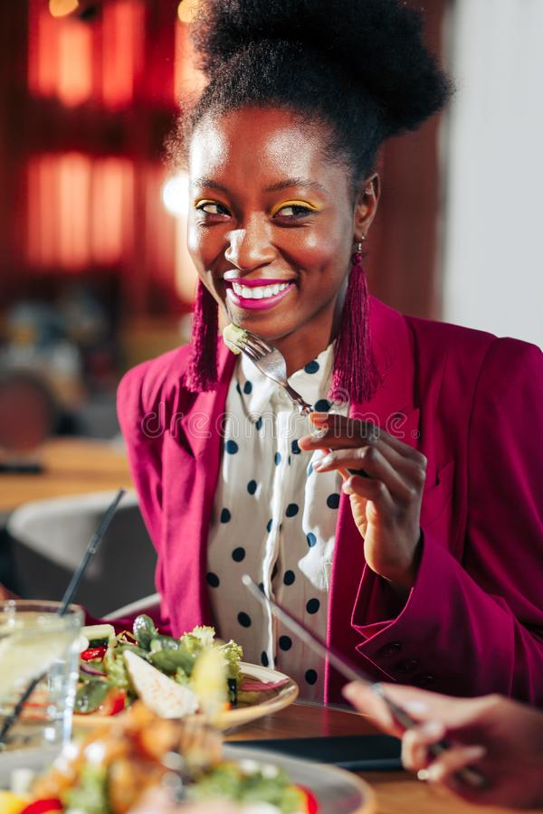 Beautiful stylish woman wearing bright jacket and pink earrings. Bright jacket. Beautiful stylish African-American women wearing bright jacket and pink earrings stock images