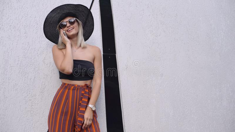 Young stylish beautiful woman in hat using a smart phone. Female talking on the phone. Beautiful stylish young blonde woman smoking cigarettes outdoors in han royalty free stock photo
