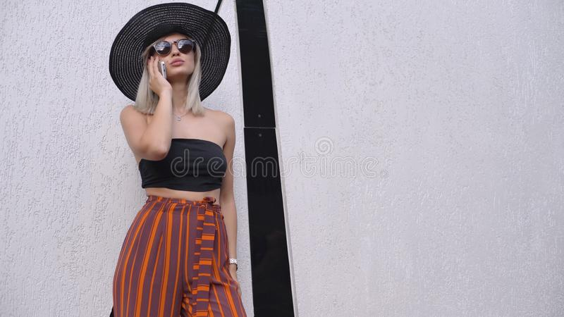 Young stylish beautiful woman in hat using a smart phone. Female talking on the phone. Beautiful stylish young blonde woman smoking cigarettes outdoors in han royalty free stock photos