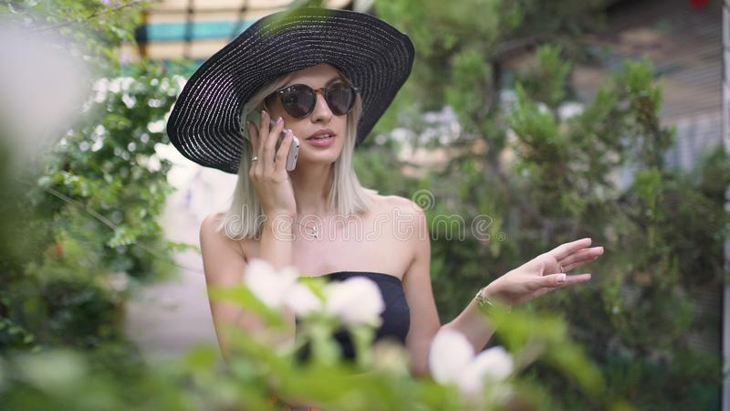 Young stylish beautiful woman in hat using a smart phone. Female talking on the phone. Beautiful stylish young blonde woman smoking cigarettes outdoors in han royalty free stock photography
