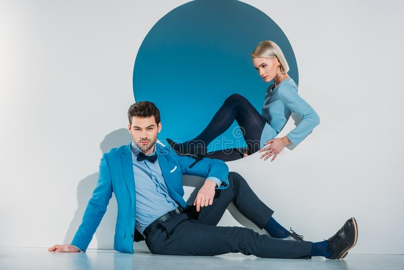 Beautiful stylish young couple in blue suit and dress sitting near opening. On grey royalty free stock image