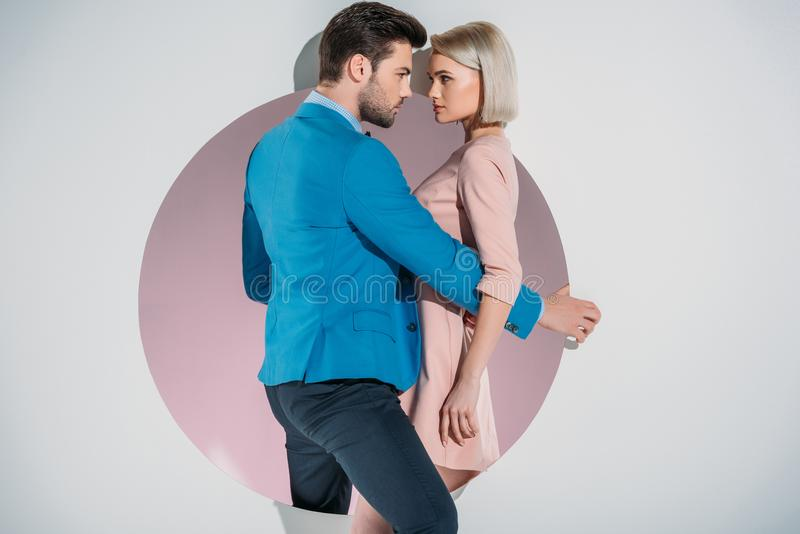 beautiful stylish young couple looking at each other while standing on hole stock photography