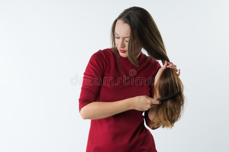 Beautiful stylish young girl combs her hair with a comb. stock images