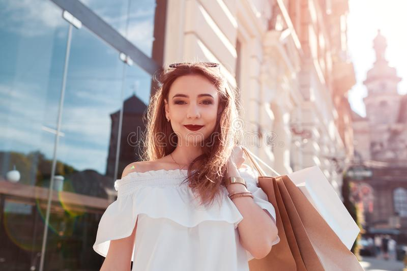 Beautiful stylish young woman with shopping bags walking on city street in summer. Happy girl holding purchases royalty free stock photography